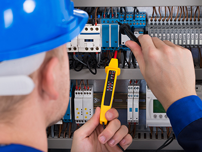 Building Management System maintenance technician investigating a fault in a mechanical services switch board with a volt meter