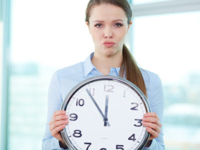 Lady executive holding a large analogue clock