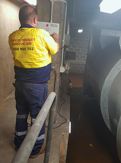 Maintenance Defined | Forte asset services Team member working on sump pump after basment flood in Sydney CBD building